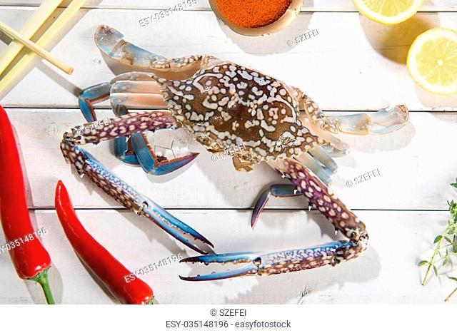 Above view raw blue crab and ingredients ready to cook, on bright wooden background