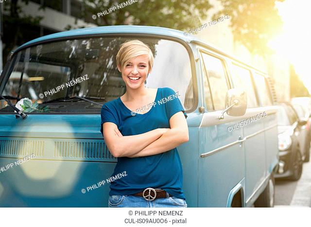 Portrait of young woman leaning against parked campervan