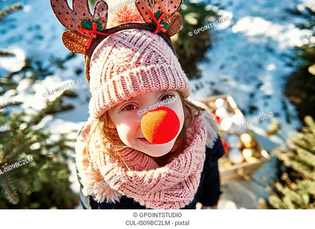 Girl in christmas tree forest with red nose, high angle portrait