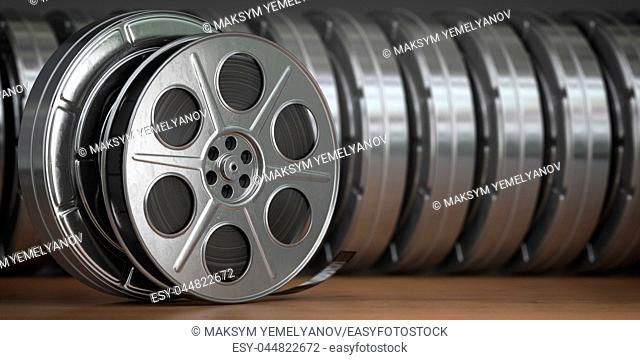 Video, cinema, movie, multimedia concept. A row of vintage film reel or film spools with filmstrip 3d illustration