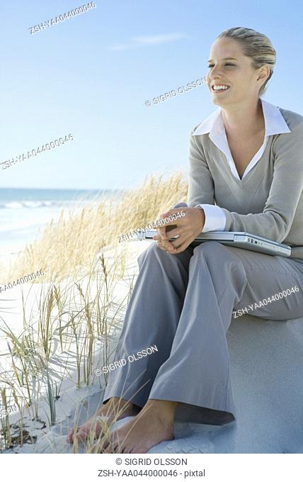 Barefoot businesswoman sitting on dune, laptop on lap, smiling