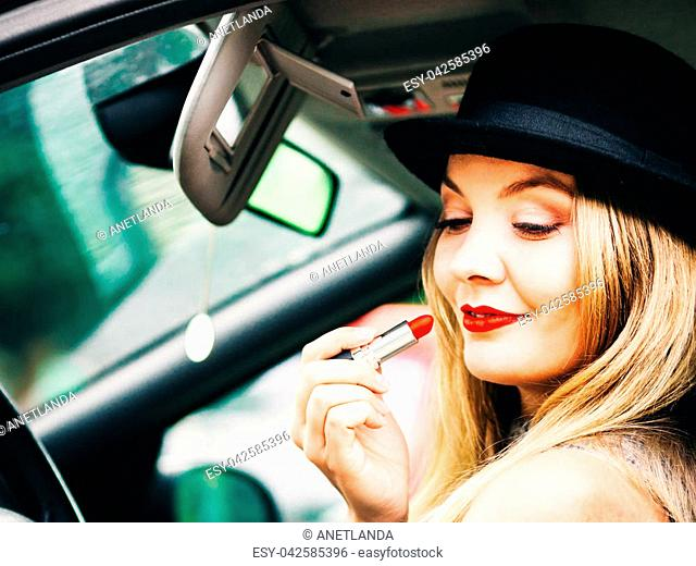 Young attractive woman looking in rear view mirror painting her lips doing applying make up while driving the car