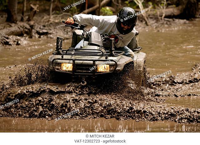 Hunter Driving All Terrain Vehicle In Mud