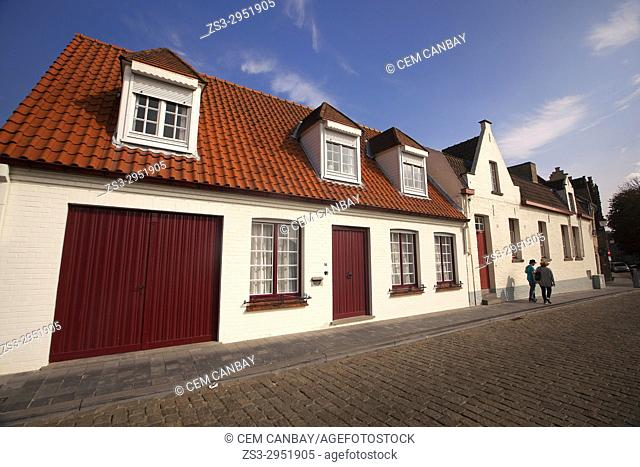 Couple walking in front of the traditional houses near the canal in the city centre, Bruges, West Flanders, Belgium, Europe