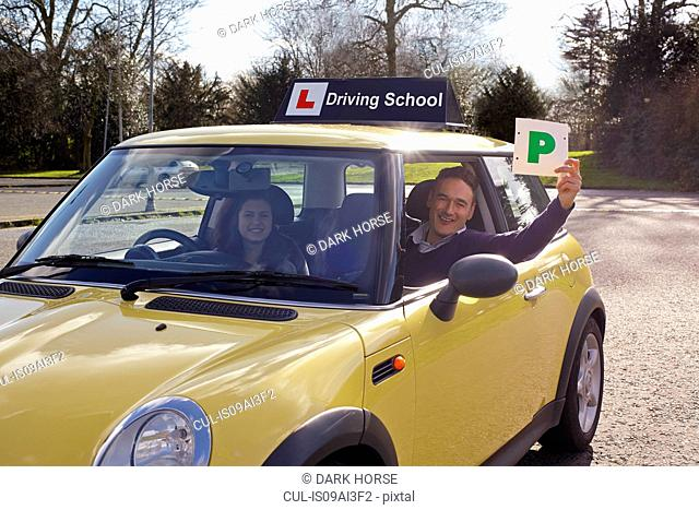 Driving instructor holding Passed Plate out of car window