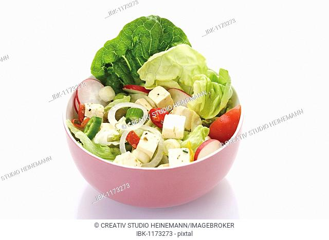 Mixed salad in a small porcelain bowl, feta cheese, feta cheese, lettuce, radishes, chives, onion, pepperoni