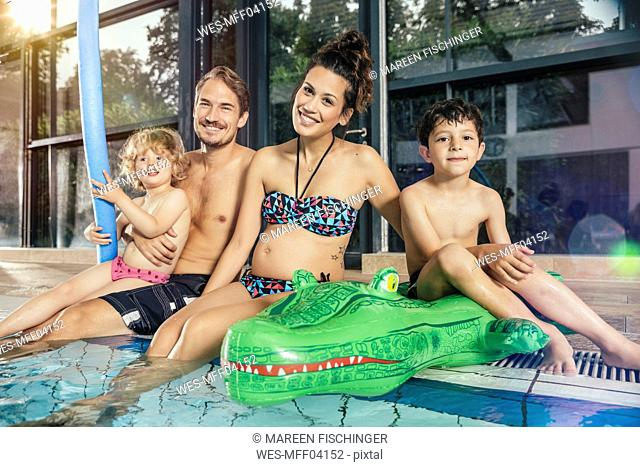 Portrait of happy family sitting on poolside in indoor swimming pool