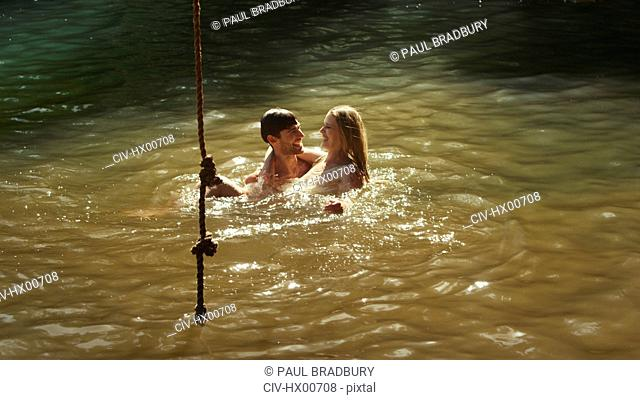 Young couple swimming in sunny lake