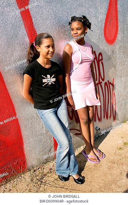 Two girls leaning against a wall in the park