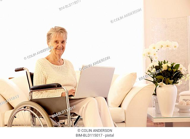 Older Caucasian woman in wheelchair using laptop