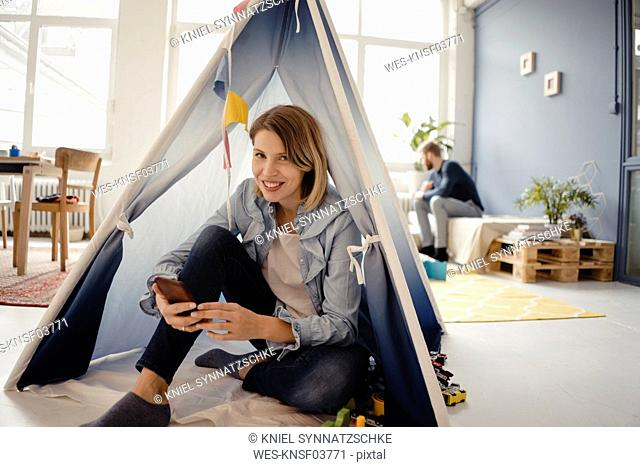Woman using smartphone in a toy tent, husband sitting in background