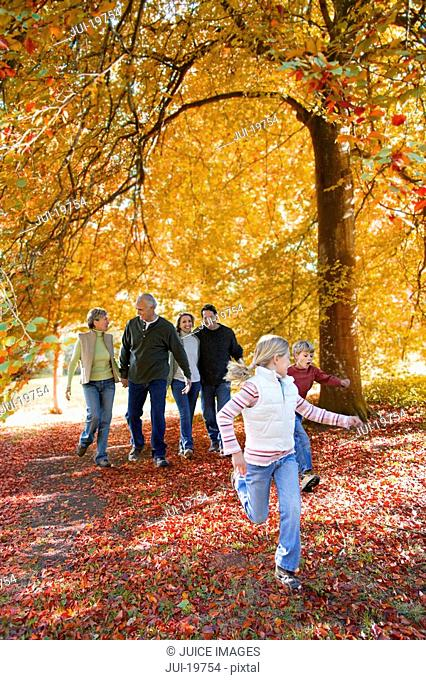 Three generation walking in park in autumn
