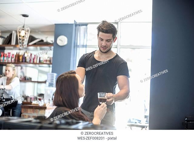 Woman in hair salon receiving cup of coffee