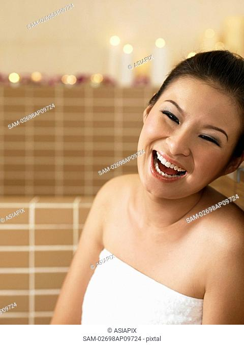 young woman in bathrobe laughing happily