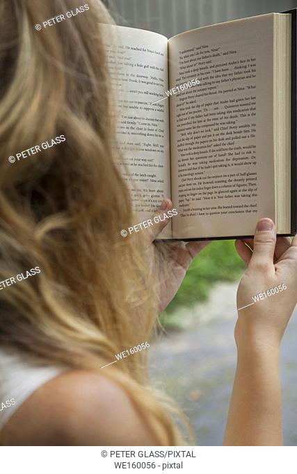 Young woman, back to camera, outdoors and reading a book