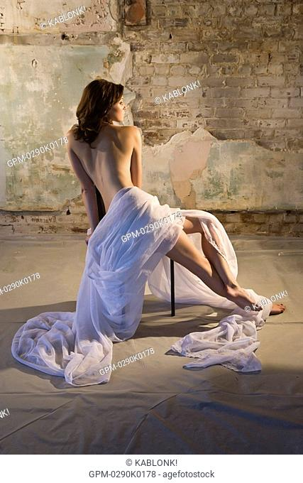 Portrait of young nude woman draped in white cloth sitting in warehouse