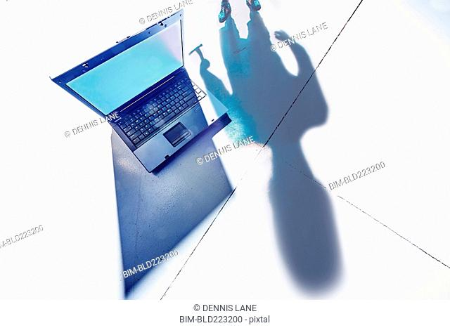 Shadow of hacker lurking over laptop computer