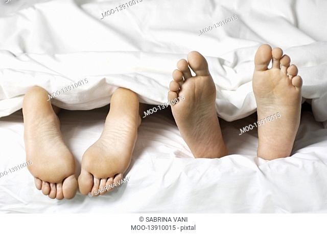 Couple lying in bed low section close up of feet