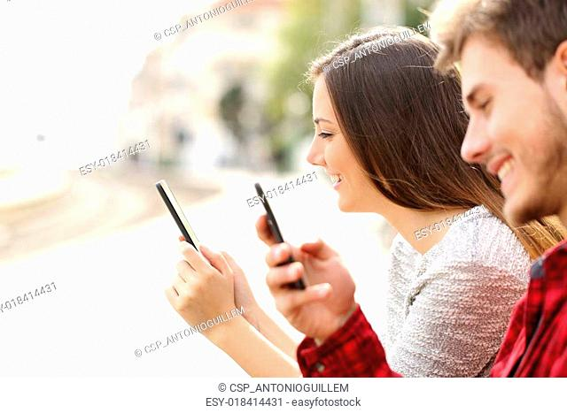 Teen couple using smart phones in a train station