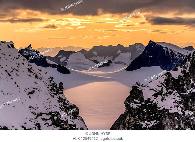 Aerial of rugged peaks and snow-covered glaciers at sunset, Juneau Ice Field, Tongass National Forest, Southeast Alaska; Alaska, United States of America