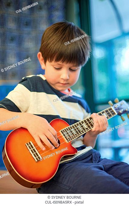Schoolboy playing ukulele in classroom at primary school