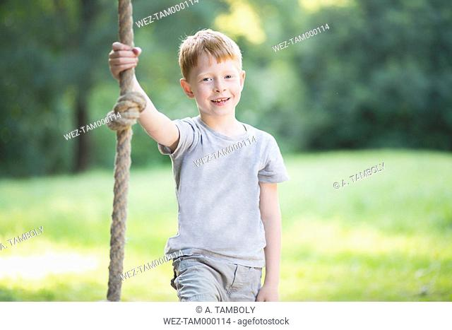 Portrait of little boy holding a rope in a park