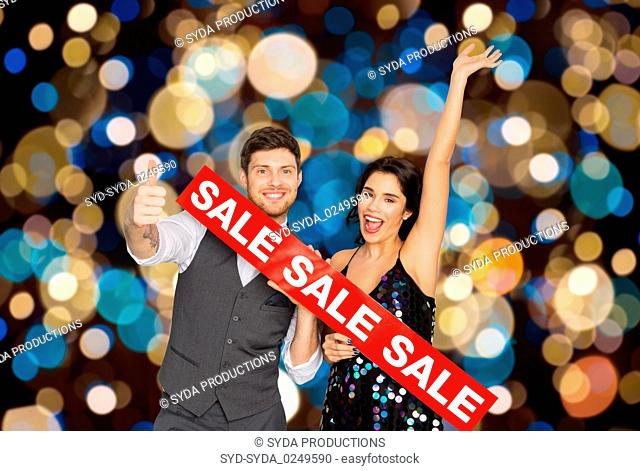 happy couple with red sale sign showing thumbs up