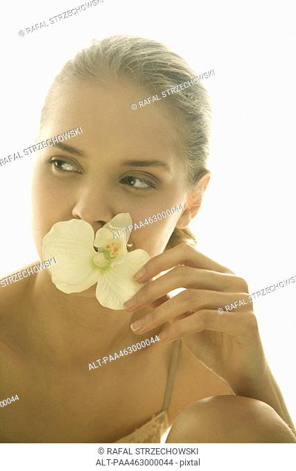 Teen girl holding up orchid flower to face