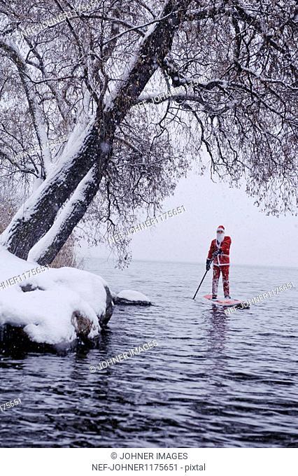 Man dressed as Santa Claus paddling on lake