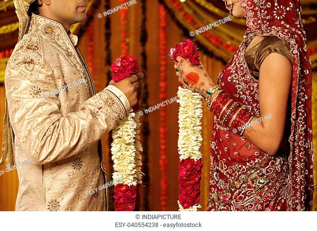 Indian bride and groom holding garlands