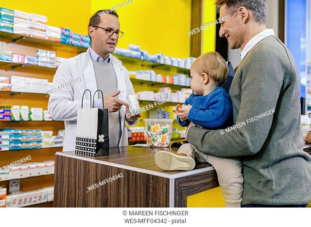Pharmacist advising father with son in pharmacy