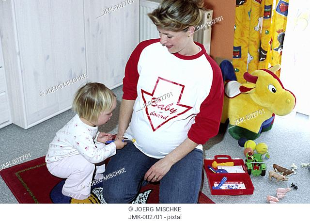 A young pregnant mother, woman, 25-30 30-35 35-40 years old, playing with her little daughter, 1-5 years old, in the nursery