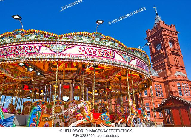 Funfair carousel ride and the pierhead building, cardiff, wales