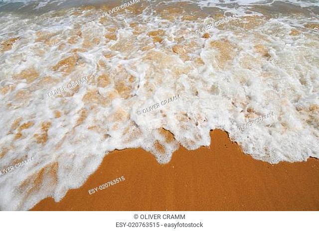 weiße Gischt auf Sandstrand