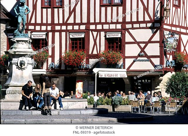 Tourists sitting in front of fountain, Dijon, Burgundy, France