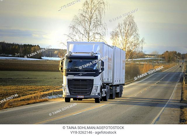 Salo, Finland - March 1, 2019: White Volvo FH truck double trailer for Posti Group, Finnish postal service on highway at sunset time in early spring