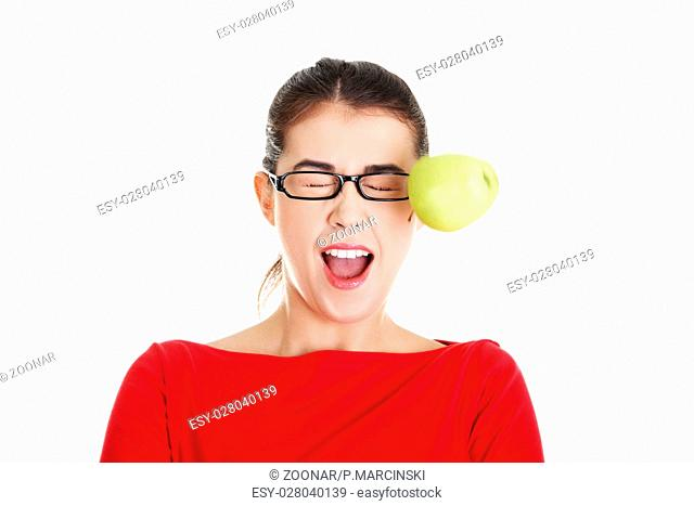 Casual woman in glasses hit by apple