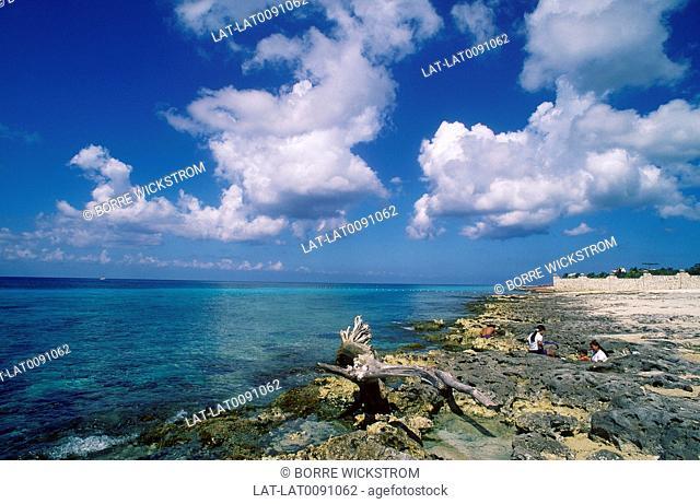 Coast. Coral rocks,beach. Clear water. Fishing nets. People on rocks