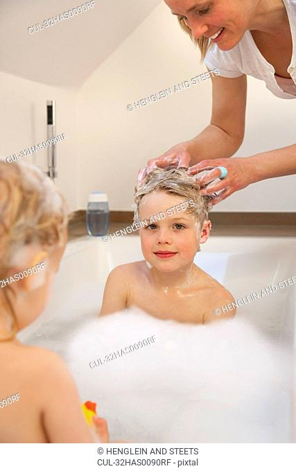 Mother washing son's hair in bathtub