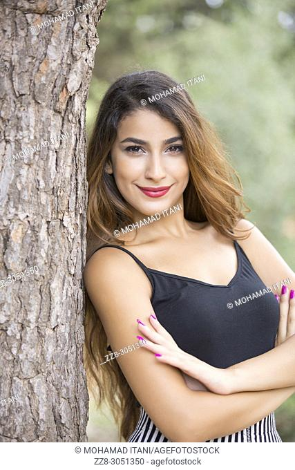 Happy young woman leaning against a tree arms folded smiling