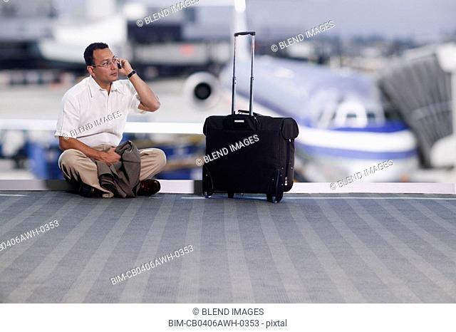 Businessman talking on cell phone at airport