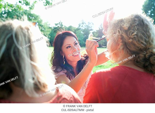 Female adult friends applying make up at sunset park party