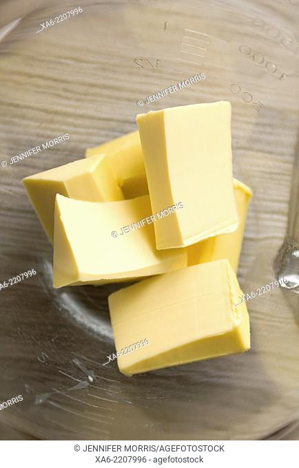 Blocks of butter sit in a glass mixing bowl