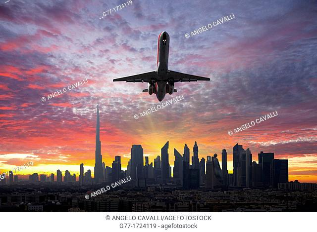 Airplane leaving a city at sunset. United Arab Emirates. Dubai