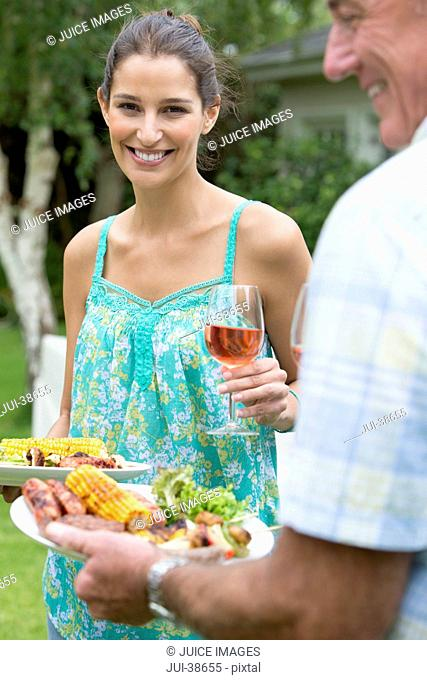 Portrait of smiling woman with plate of barbecue and wine glass