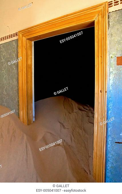 a dune coming from a door in a house at kolmanskop ghost town namibia africa
