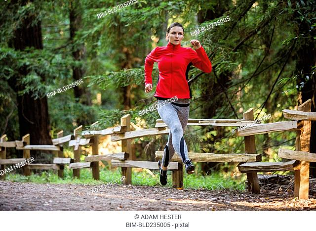 Woman running on forest path