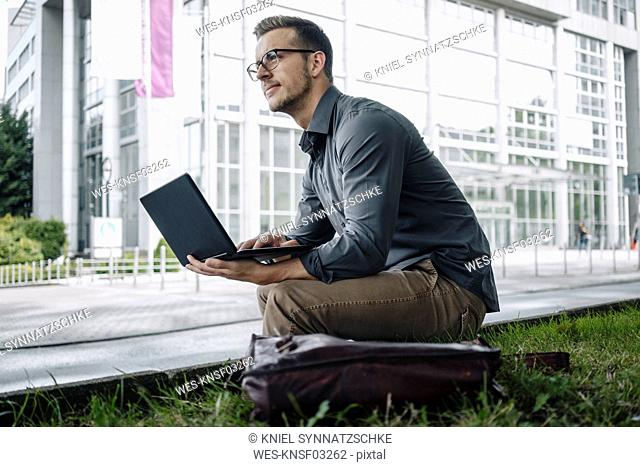 Young businessman sitting outdoors using laptop