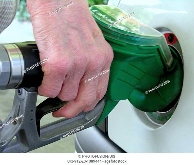 Elderly woman filling her car with unleaded petrol UK
