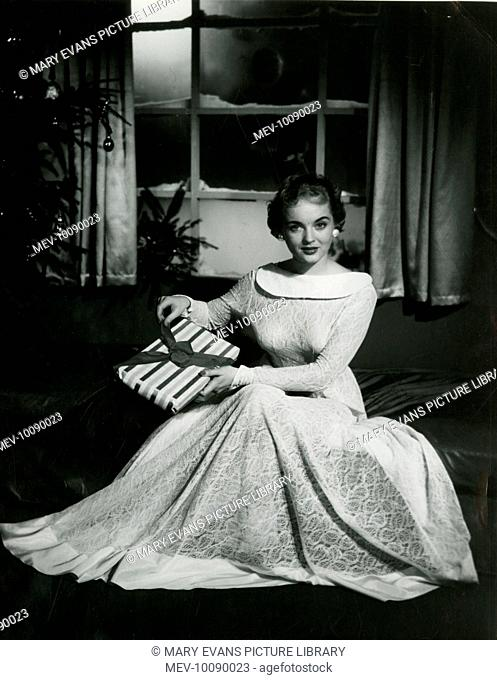 A patient woman sits with her Christmas present wrapped in stripey paper and tied with a ribbon